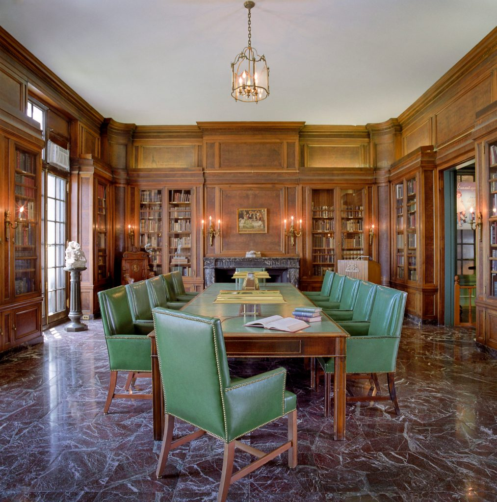 A library with bookshelves and a table in the center of the room, surrounded by 10 chairs