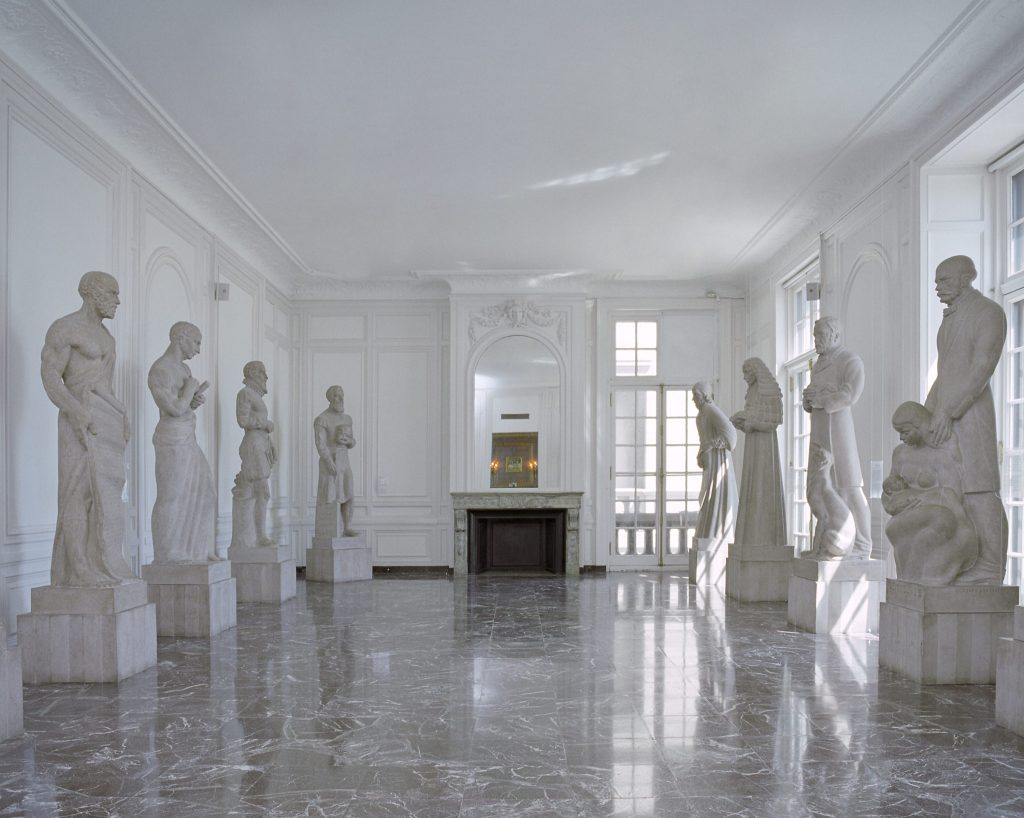 Color photo of the Hall of Immortals. Seven stone sculptures can be seen of different people from medical history.