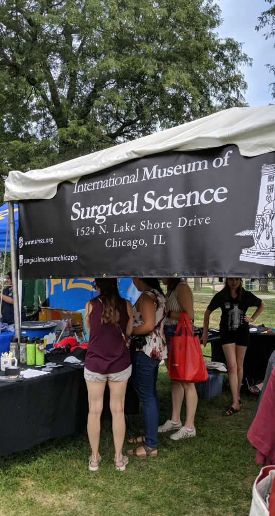 "A tent with a banner reading ""International Museum of Surgical Science"" outdoors at the 2019 Chicago Hot Dog Fest. Visitors are looking at merchandise displayed on a table."