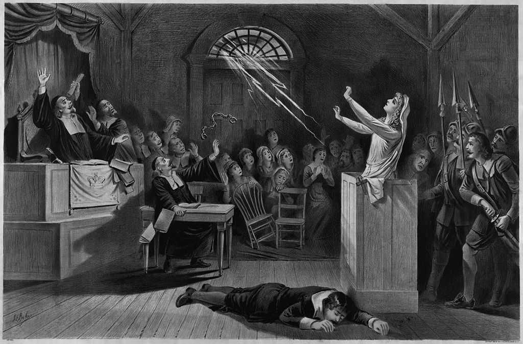 This lithograph illustration made in 1892, depicts imagined events during the Salem Witch Trials. The image shows an accused witch before the court, her handcuffs flying in the air, and lightning coming in from the window, implying that she has used her powers to attack the court.