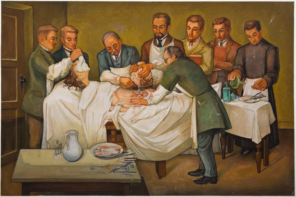 Mural from the Obstetrics and Gynecology exhibit that commemorates the first ovariotomy performed in Colombia. Eight male doctors surround the patient who is  fully anesthetized, likely by an ether or chloroform-soaked cloth that covers her face. The anaesthesiologist works at a table in the corner.