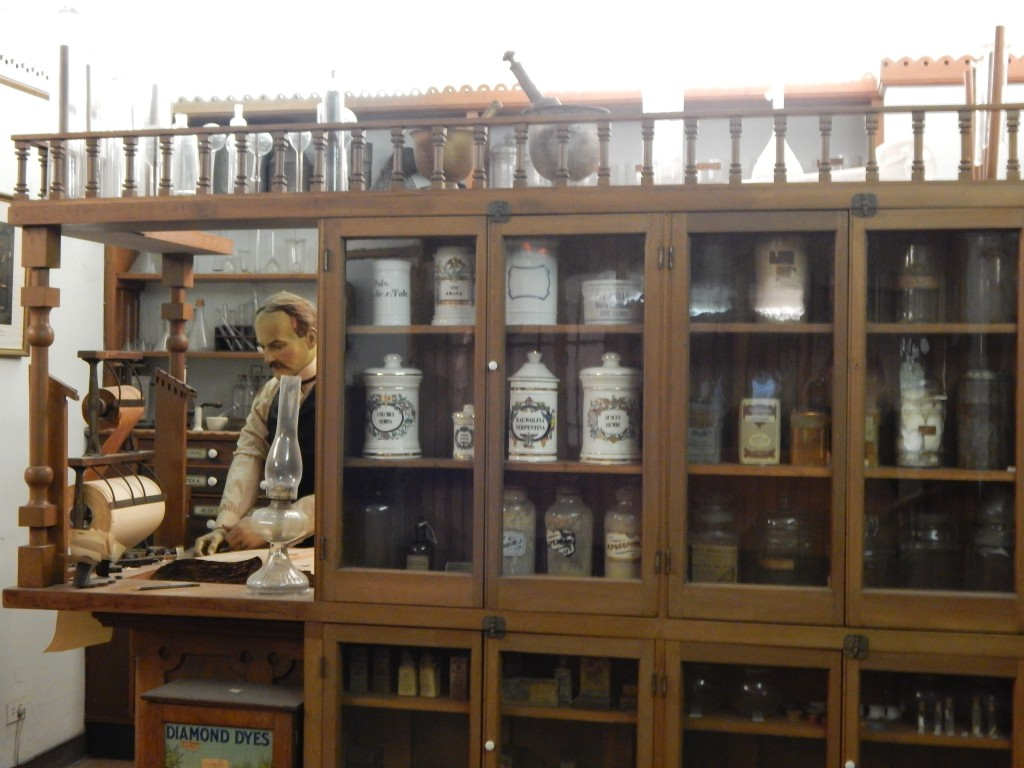 This image is from the IMSS Apothecary exhibit, which recreates a nineteenth-century apothecary. This time period was particularly known for patent medicines such as Mrs. Winslow's. The image shows a mannequin of a doctor behind a counter, with shelves of medications.