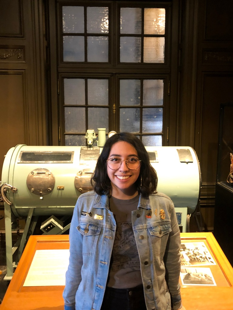 Image of education intern, Jackie, in front of the Iron Lung